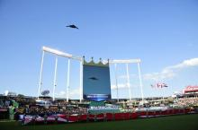 A nuclear-capable B-2 Stealth Bomber flies over a gigantic flag at the 2012 Baseball All-Star Game