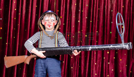 Young-boy-wearing-clown-make-up-and-military-helmet-standing-on-stage-with-red-curtain-aiming-over-s